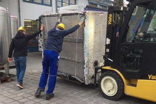 Mit Maschinen- und Muskelkraft: Stück für Stück wird die Brauanlage entladen.